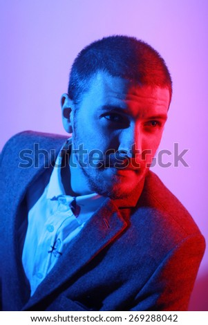Portrait of handsome casual stylish young man in suit in blue and red colored lights - stock photo