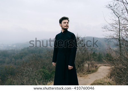 Portrait of handsome catholic bearded priest or pastor posing outdoors in mountains