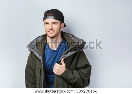 Portrait of handsome caucasian man standing on grey background. Young man with jacket and cap showing thumb up - stock photo