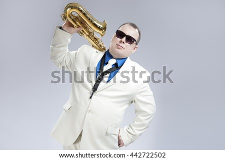 Portrait of Handsome Caucasian Saxophone Player With Music Instrument Over Shoulder. Posing Against White.Horizontal Image Orientation - stock photo