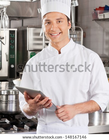 Portrait of handsome chef with tablet computer in commercial kitchen - stock photo