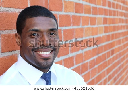Portrait of handsome confident young African businessman standing smiling happy, looking at camera - stock photo