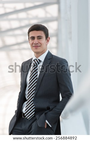 Portrait of handsome confident young businessman standing arms in pockets, smiling happy, looking at camera. - stock photo