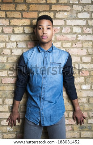 Portrait of handsome dark skinned male model wearing casual clothes against brick wall - stock photo
