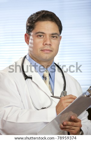 Portrait of handsome doctor in the office writing on chart. - stock photo