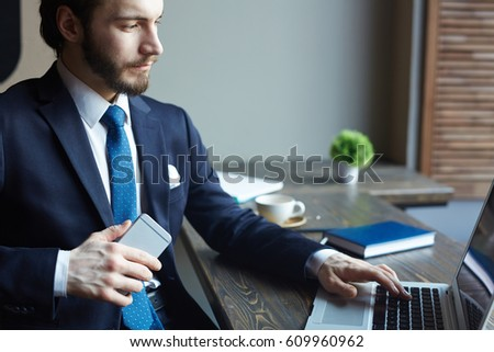 Portrait of handsome elegant businessman busy working with laptop and smartphone at wooden table in cafe