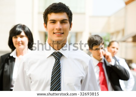 Portrait of handsome employer looking at camera with smile on background of business team - stock photo