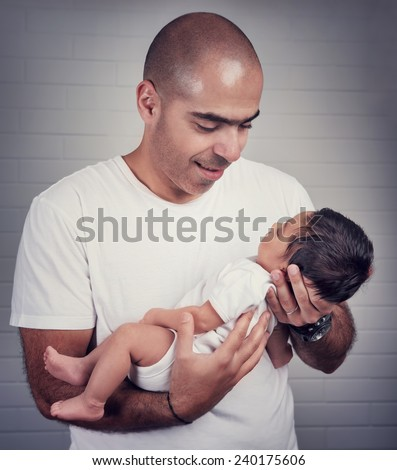Portrait of handsome father holding on hands cute little baby, spending time at home, lovely young family, love and happiness concept - stock photo
