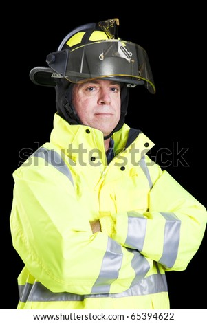 Portrait of handsome firefighter taken against a black background. - stock photo