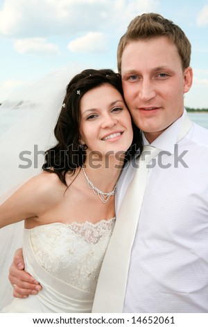 Portrait of handsome groom hugging his beautiful bride