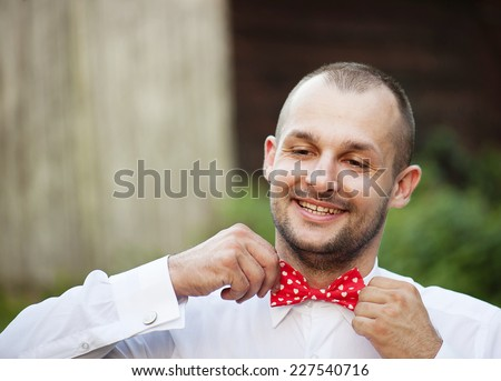 Portrait of handsome groom in the park getting ready for the wedding. - stock photo
