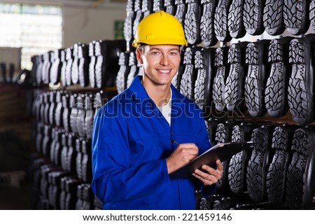 portrait of handsome gumboots factory quality controller - stock photo