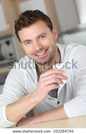 Portrait of handsome guy drinking coffee in home kitchen - stock photo