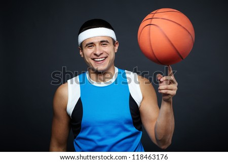 Portrait of handsome guy in sportswear with basket ball on his forefinger looking at camera - stock photo