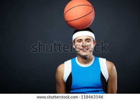 Portrait of handsome guy in sportswear with basket ball on his head looking at camera - stock photo