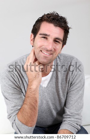 Portrait of handsome guy with hand on chin - stock photo