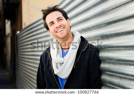 Portrait of handsome happy man in urban background - stock photo