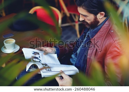 Portrait of handsome hipster man read magazine during his breakfast on the terrace of coffee shop, filtered image - stock photo