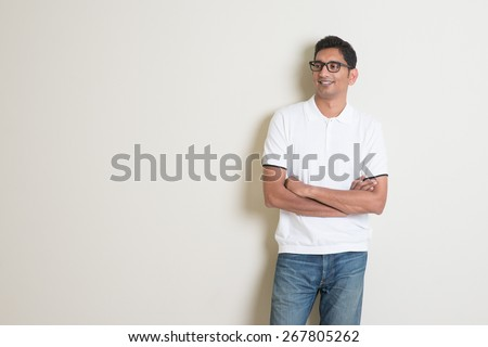 Portrait of handsome Indian guy standing on plain background, looking at copy space at side. - stock photo