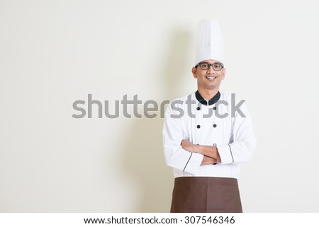 Portrait of handsome Indian male chef in uniform smiling, standing on plain background with shadow, copy space at side. - stock photo