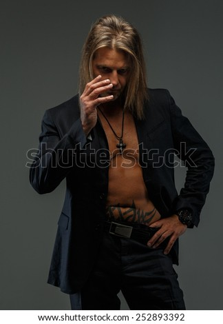 Portrait of handsome long-haired man wearing dark grey suit on naked torso. Isolated on gray background. - stock photo