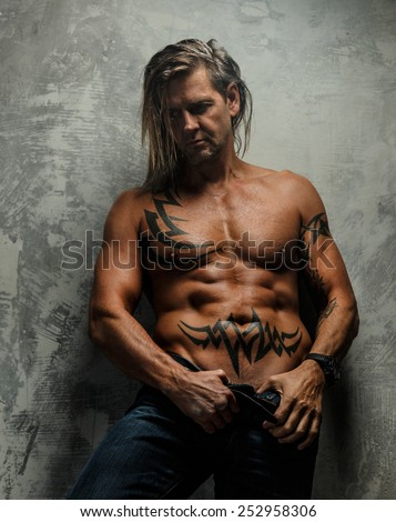 Portrait of handsome long-haired man with naked torso. Isolated on gray background. Tattoed male body. - stock photo