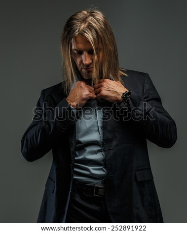 Portrait of handsome long-haired stylish man in dark grey suit. Isolated on gray background.