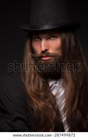 Portrait of handsome magician performing black magic. Man with long hair and top hat isolated on dark background. - stock photo