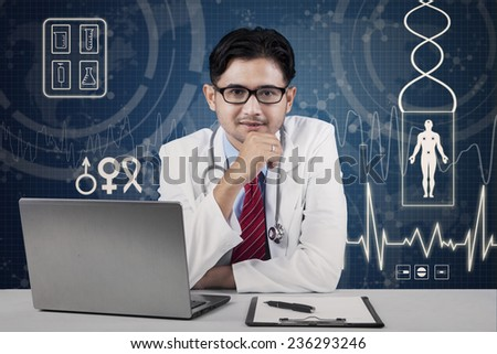 Portrait of handsome male asian doctor smiling at camera - stock photo