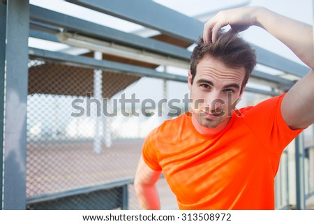 Portrait of handsome male athlete in fluorescent copy space t-shirt rest after active training in sunny afternoon outdoors, sports build caucasian man taking break after evening run in urban setting - stock photo