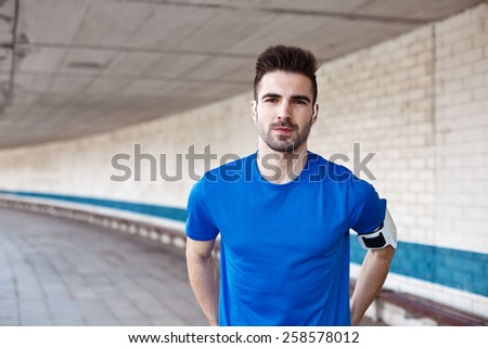 Portrait of handsome male athlete with stubble in blank t-shirt and earphones - stock photo