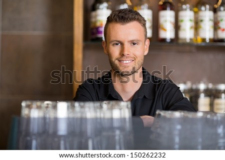 Portrait of handsome male barista at coffeeshop - stock photo