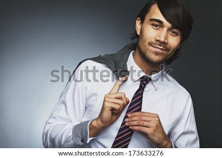 Portrait of handsome male entrepreneur holding his coat over shoulder looking at camera smiling. Asian businessman looking relaxed against grey background. - stock photo
