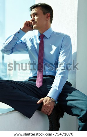 Portrait of handsome man calling by mobile phone in office