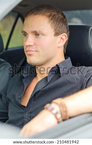Portrait of handsome man in the car.