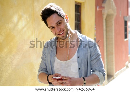 Portrait of handsome man in urban background listening to the music with headphones - stock photo