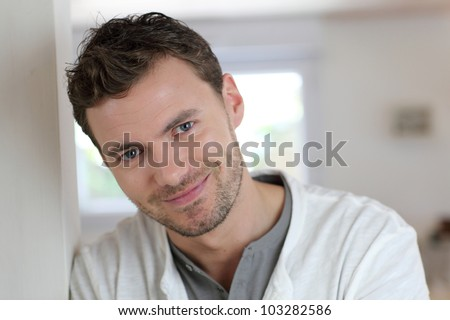 Portrait of handsome man leaning on wall - stock photo