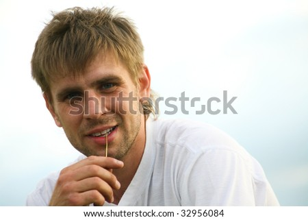 Portrait of handsome man looking at camera on a sky background - stock photo