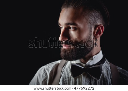 Portrait of handsome man posing for photographer in studio
