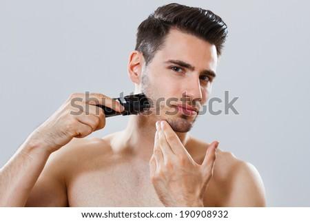 Portrait of handsome man shaving his beard,Shaving the beard - stock photo