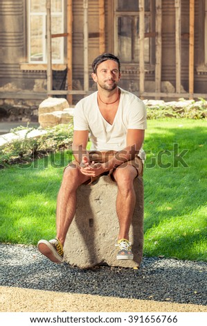 Portrait of handsome man sitting down on stone and posing outdoors - stock photo