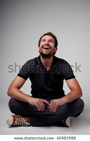 Portrait of handsome man sitting with crossed legs - stock photo