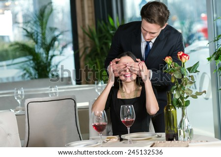 Portrait of handsome man spending time in restaurant with his wife. He is prepared to give present for his beloved wife - stock photo