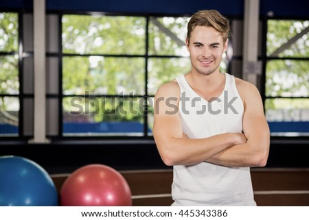 Portrait of handsome man standing in gym with arms crossed - stock photo