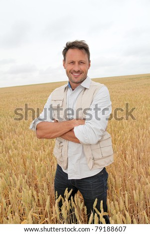 Portrait of handsome man standing in wheat field - stock photo