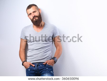 Portrait of handsome man standing, isolated on grey background - stock photo