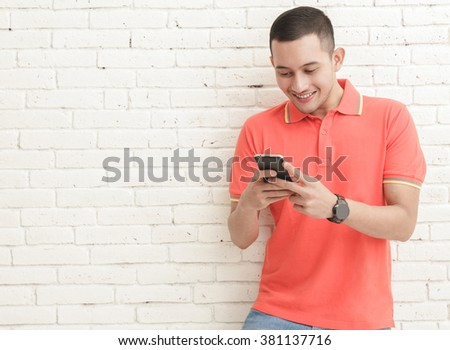 portrait of handsome man texting on mobilephone with copy space on white brick wall background - stock photo