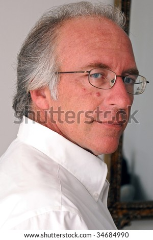 portrait of handsome man turned looking at viewer with a slight smile in white dress shirt. - stock photo