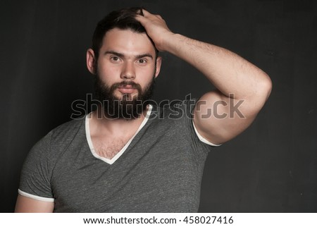 Portrait of handsome man with beard. Confident muscular man in t-shirt
