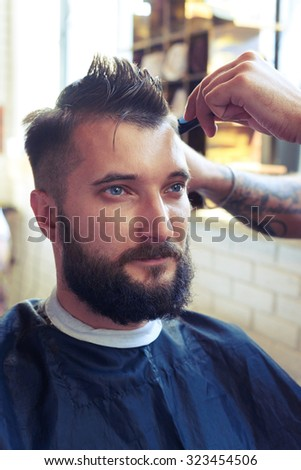 portrait of handsome man with beard in barber shop. barber cutting hair with scissors and comb - stock photo